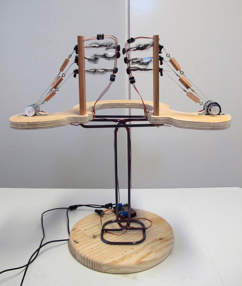 Lessner, L. (2019). Beijos de Borboleta. Interactive sculpture: carnaval eyelashes, wood, metal, PLA, motors, microcontroller. 22 x 19.5 x 13 in.