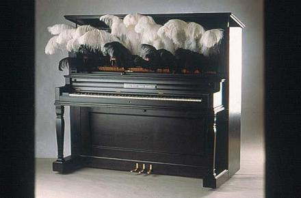 """Johnson, Carla Rae. (2004). Bessie Smith Meets Beethoven (front view). Sculpture. Piano, digital drawings and plumes. 58""""x60""""x27"""". Photography by Howard Goodman."""