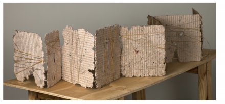 """Ruff, D. (2019). Fourth Estate. Books series. Financial Times, matte medium, twine, linen thread, sage. 10 x 48 inches. """"Fourth Estate"""" refers to the press. This book references the attack on journalism, the death of print journalism, while suggesting a wall- not the wall on the border, but the wall of protection from lies and distortion that the press represents."""